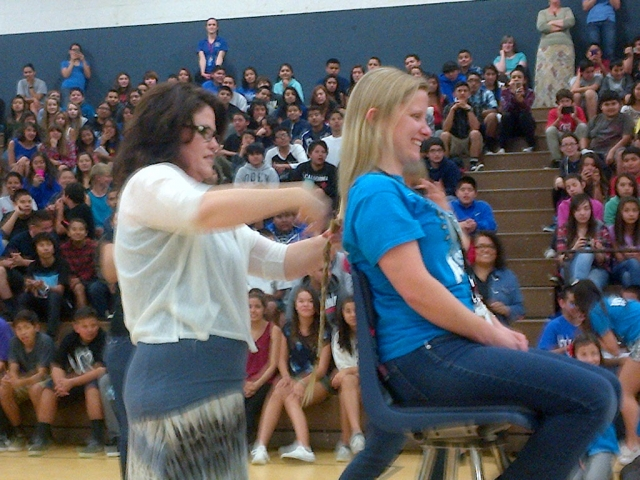 "Fillmore Middle School held their spring rally on Friday, March 14th. The Associated Student Body (ASB) planned and led the rally which included two teachers, Mrs. Nichols and Ms. Dyer, cutting their hair to donate for cancer victims. In February FMS students raised over $2,000 in the Pennies for Patients Fundraiser. The charity raises money to support the families of cancer victims as well as cancer research. After a brief ""dance off"" to break the tie, the 8th grade class won the rally. Pictured above, Ms. Dyer as her hair is cut for charity."