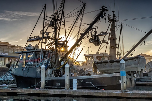 "Photo of the Week: ""Ventura Harbor commercial fishing boat & sunstar in building tower"" by Bob Crum. Photo data: Canon 7DMKII camera, manual mode, Tamron 16-300mm lens @24mm. Exposure; ISO 800, aperture f/20, 1/320 second shutter speed."