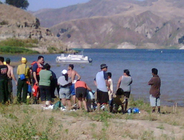 A crowd gathers to watch the attempted rescue of Denise Arredondo, of Piru, Saturday. Denise drowned after wading into the lake while on a family picnic.