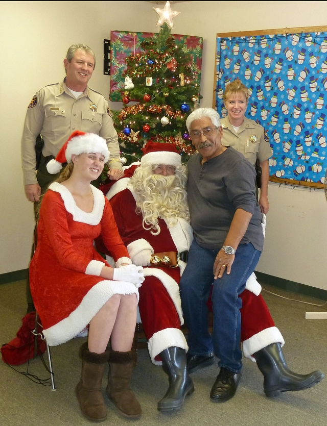 Christmas at he Fillmore Police Storefront Tuesday brought out the child in all who were there. Pictured (standing left) is Sheriff Geoff Dean, Santa and his helper, Community Resource Officer Max Pina, and Fillmore Capt. Monica McGrath.