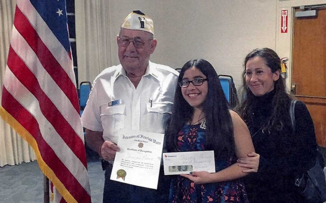 "The Fillmore Veterans of Foreign Wars presented Shaina Ponce with a certificate of appreciation and $100 for her first place entry in the VFW ""Voice of Democracy"". The Voice of Democracy contest is open to all high school students within the Fillmore Unified School District. This year's theme was ""My Vision for America."" Shaina took first place at the Fillmore VFW Post level. Pictured (l-r) are Commander Jim Rogers, Shaina Ponce and her mother Irene Madrigal."