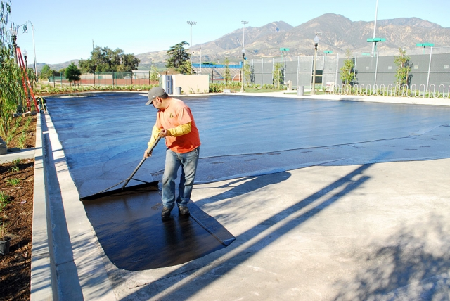 A worker seals the asphalt at the new swimming complex on First Street.