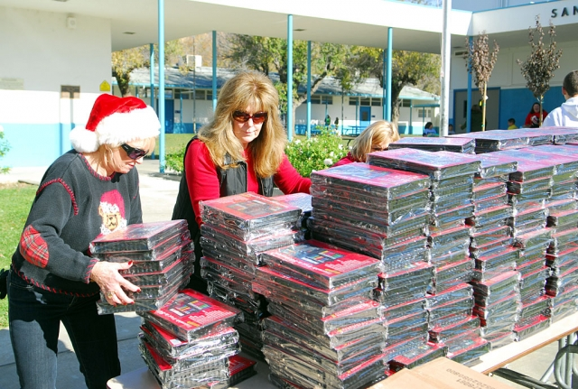 Lynda Miller, right, founder of the Support for the Kids Foundation, readies just some of the many gifts distributed to students at San Cayetano and Piru Elementary through the foundation.