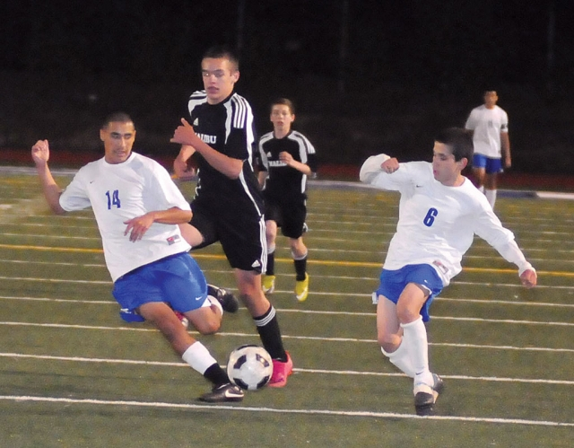 Bryan Ayala #14 and Jose Garcia #8 work together to keep the ball away from Malibu.