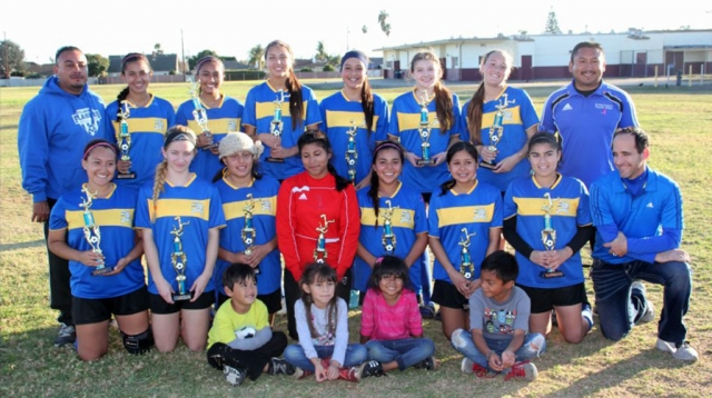Players and coaches, (l-r) (bottom row) Rachel Rivera, Sarah Volmert, Lizette Martinez (Nena), Salma Gomez, Ana Rincon, Jocelyn Munoz, Caroline Esquivel, Coach Willy, (top row) Coach Homer Martinez, Grace Topete, Reylene Martinez, Emily Garnica, Esmeralda Murillo, Vanessa Estrada, Ryan Nunez, Coach Arnold Munoz. Little cheer squad: Isaac Martinez, Maddie Munoz, Mia Munoz, Adrian. Players missing from photo: Briana Santa Rosa, Denise Vasquez, Betty Morales.