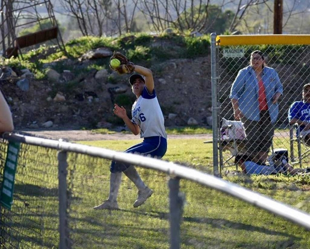 Senior Leah Meza makes a great catch in foul territory. Photo credit Betolu Photography.