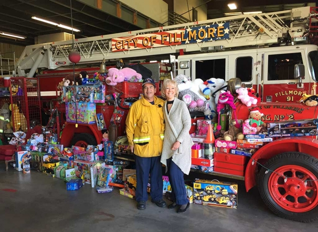 Fillmore Assistant Fire Chief Bill Herrera standing with Jane David who dropped off toys that the International Soroptimist of Fillmore collected from their Annual Fashion Show, Saturday, December 9th. Read more in Letters to the Editor on page 2. Photo courtesy Fillmore Soroptimist Club. Photo courtesy Jane David.