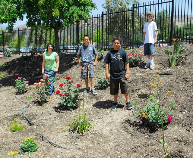 A beautiful Memorial Garden has been created by the teacher Laurie Merrill's 3rd period class. Shown are just four of the students who participate in the garden project: (l-r) Silver Perez, Isaiah Martinez, Isaiah Mendez, and Justin Beach, who is working on a video of the project.