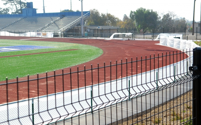 According to Bob Sube, who supervises Fillmore School District structure development, the high school track is undergoing significant corrective surgery. The all-weather track, which is composed of several layers of rubber particulate and a clear synthetic over-sheet sprayed with grit for traction, was not level. The lower spots collected water and made the surface less suitable for runners. This was the second major flaw discovered by Bob Sube. The first problem was related to sub-standard artificial turf. The entire playing field had to be removed and replaced. The cost was covered by warranties in the construction contract, as was the cost of leveling the track. The final coating for the track should be finished this weekend. The total cost of these corrections is estimated to be near $200,000. Mr. Sube has done an exceptional job of overseeing the District's new construction. The Gazette recently found him checking-out Sespe School's new playground equipment on his day off. He saw to it that a proper border was poured and a soft layer of material was placed under the equipment before it was put into use. This playground is avidly used by children from kindergarten through second grade.