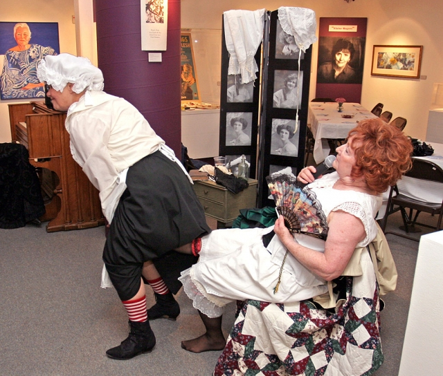 "In the Victorian era, taking off shoes and all the other underpinnings, was quite a chore as ""Phoebe"" (Dotty Wheeler) attempts to do for her ""lady"", ""Mrs. Horace Swazey"" (Dorothea Phelan). (photo: Roger Conrad)"