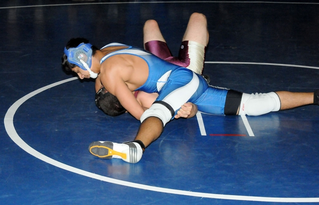 Kyle Castaneda attempts to pin his opponent during Tuesday night's match.