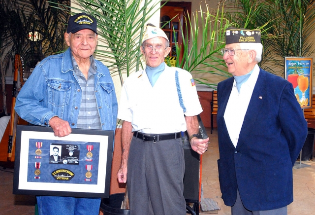 Shown (l-r) are John Garcia with a replica plaque, Dick Schuck and Bud Untiedt, all three veterans of World War II.