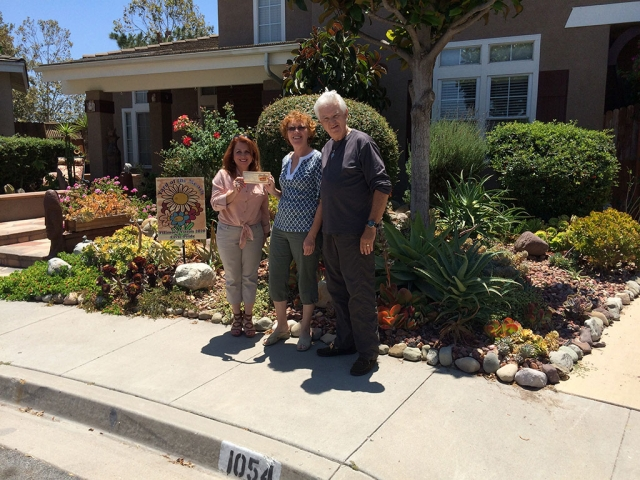 Theresa Robledo presents the Fillmore Vision 2020 Civic Pride's Yard of the Month for July to Mr. and Mrs. Fitzgerald