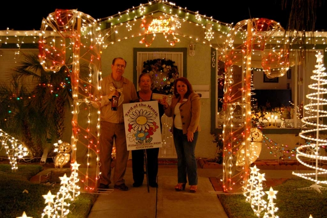 "Theresa Robledo (right) presenting the Fillmore Vision 2020 Civic Pride December 2016 ""Yard of the Month"" award to Mr. & Mrs. Melgoza, along with a gift certificate from Otto & Sons Nursery. Congratulations to Mr. and Mrs. Melgoza at 360 C Street, their lovely Christmas Décor lights up the corner of C Street and Sespe!  Please drive by and view for yourself, the Melgozas have been decorating their home for many years, and we were invited inside their home to view all the beautiful décor of their Christmas Village!  The Melgozas were awarded a gift certificate from Otto & Sons for $40 and a bottle of wine from the Robledo Family Winery and Diamond Realty.  What Christmas cheer this home brings to our community and we thank our community that participate every year!   Fillmore Vision 2020 Civic Pride would also, like to make known honorable mentions: Edgewood and Taylor Lane, there are so many more in our community, feel free to take the family out for a tour in the evening to usher in the Christmas spirit!"