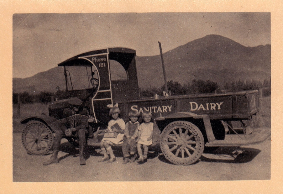 Sanitary Dairy truck in 1925, with Cliff, Dorothy, Russell and Evelyn Hardison sitting on the truck. Children would jump on and off the running boards to deliver milk.
