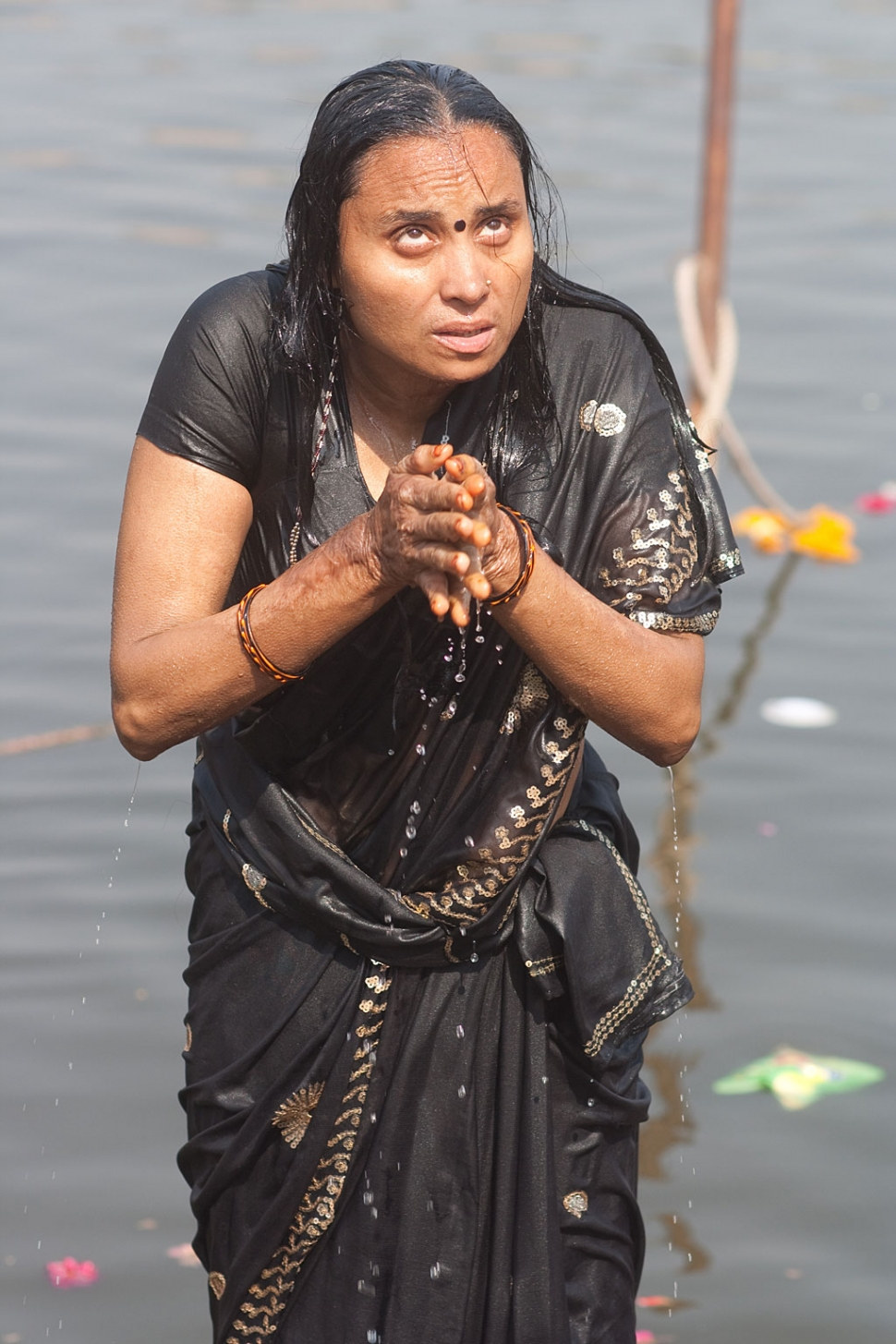 A woman offering up prayers as part of her morning puja on the bathing ghat in Ujjain, Madhya Pradesh. Photograph by Paul Hanson.