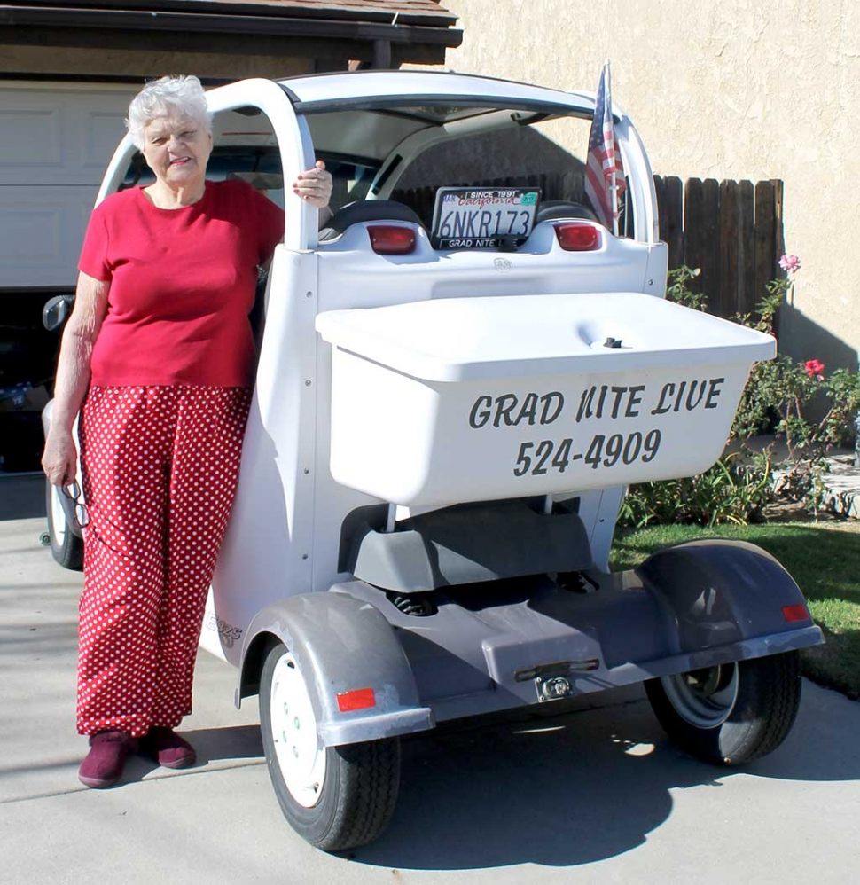 "Mrs. Chaney standing next to the infamous Grad Nite Live Electric Car. Mrs. Chaney said, ""It is with a heavy heart I am selling my electric car (Grad Nite Live). I can't drive any more so it sits. It needs some TLC and batteries. I drove 10,000 miles since 2002 and never left Fillmore. It will be nice to see my GEM out and about in Fillmore again. Thanks for waving at me all those years."""