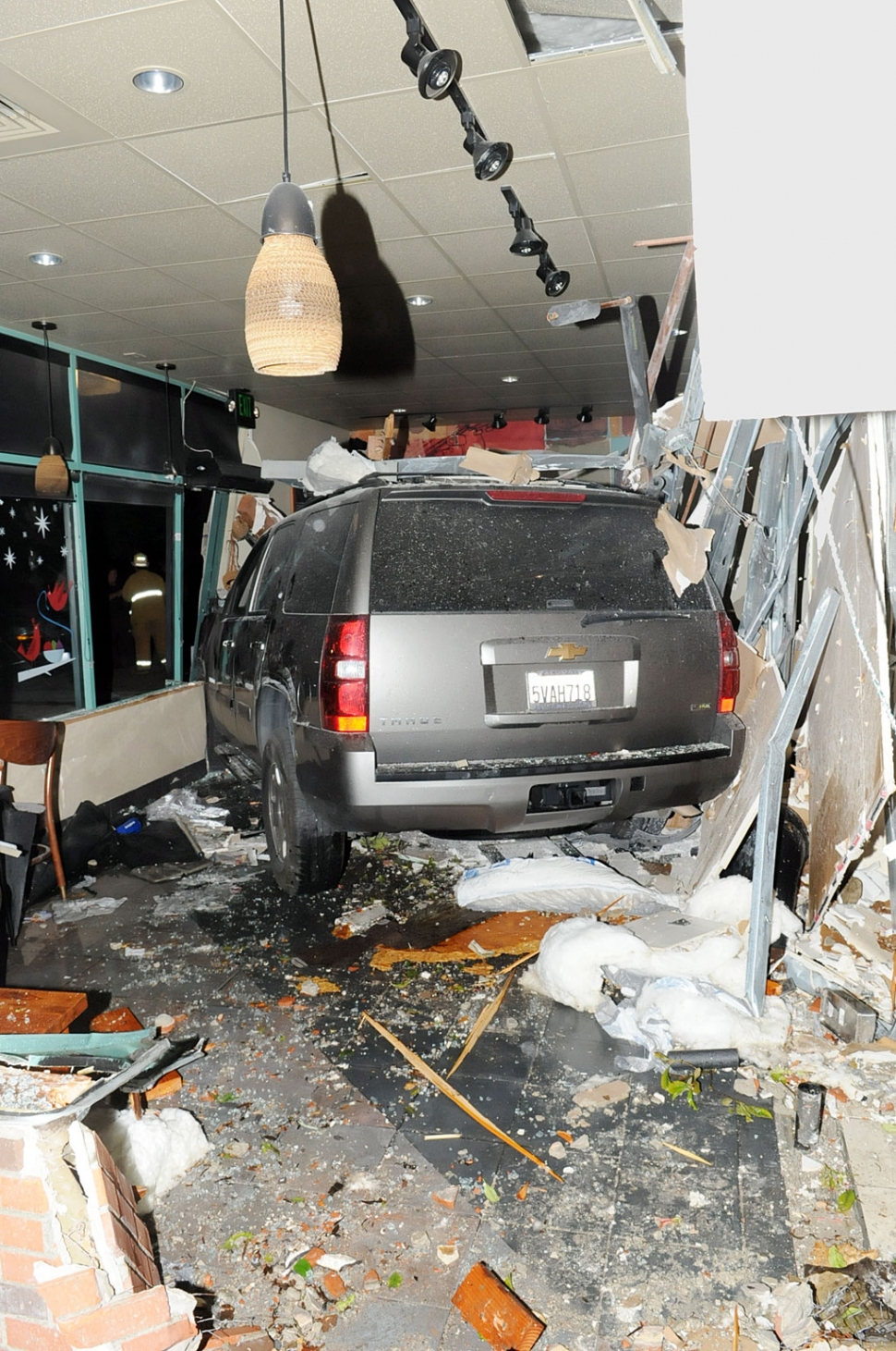 At approximately 7:07 p.m. on Tuesday December 13th, 12 Fillmore Fire units responded to a vehicle collision at Starbucks in Fillmore at the corner of A street and Highway 126. A Chevrolet Tahoe had crashed through the east wall of the business, near the drive thru, pinning several people against tables and walls. Eye witnesses said the vehicle was traveling about 50 miles per hour when it struck the building's exterior wall. The driver identified himself as a Los Angeles Sheriff's Department deputy. He stated he had fallen asleep and veered from the westbound lanes of Highway 126 (Old Telegraph Road) across the eastbound lanes, over the sidewalk, across the parking lot for approximately 100 yards, between two large palm trees before crashing through Starbucks east wall. The vehicle traveled completely through the front lounge coming to rest against the front door and corner. One unidentified man who was sitting in a large brown chair on the east wall of the building near the point of impact was pinned against the front door on the opposite side of the dining area. His injuries were reported to be critical. Two other patrons were seriously injured when they were pinned against the south wall of the dining area. All three persons were extracted by the Fillmore Fire Department and transported a local hospital, according to Fire Chief Rigo Landeros. We will have an update as more information becomes available.