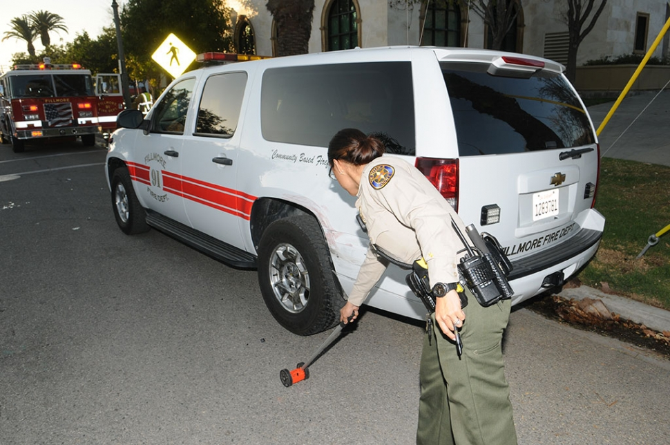 A Ventura County Sheriff marks off the location of a hit & run, which occurred on Wednesday, January 3, at approximately 4p.m. Fillmore Fire Chief Rigo Landeros' city truck was parked at the curb on Santa Clara Avenue, just south of City Hall. A citizen witnessed the collision, telling Landeros it was a red truck, heading west-bound. Red paint was found on the city vehicle at the site of impact. Ventura County Sheriff Deputies located the red truck just east of Palm Street. No further details were available.