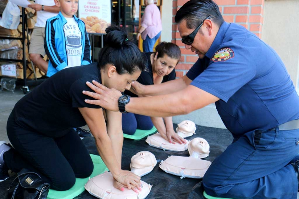 "Fillmore Fire Department had a wonderful turnout of over 80 individuals who participated in the Hands Only CPR event in front of Vons on the 600 block of Ventura Street Thursday, June 2nd. By teaching community members Hands-Only CPR, more victims of sudden cardiac arrests will have bystander performed CPR and will be more likely to survive. Customers who were approached and invited to participate were instructed on proper steps to Hands Only CPR. They were taught to check for responsiveness: shaking and shouting ""Are you okay?"": followed by calling 911 or having someone else do so if the individual is unresponsive and breathing slowly or not at all. Compress: Position on the floor face up. Kneel right next to the person - so your knees touch his/her arm. Place the heel of one hand on the center of the chest at the sternum and the other hand on top of the first. Lock your elbows put your shoulders over the center of the chest and push HARD straight downward - at least 2 inches. Lift your hands off the chest slightly after each compression to allow the chest to fully re-expand. Compress fast at a rate of 100 per minute. Continue until EMS arrives. Don't stop if the person gasps it is not a sign of recovery - it's because you are doing a good job with CPR. When you tire switch off with other people. Many people are concerned they might do something wrong, but the only way to make things worse is by doing nothing. Some of the participants had expressed past experiences where this would have been helpful and possibly life saving for their friends and family members. This event proved to be very well received and appreciated by the community. Pictured is Firefighter David Biazon. Photo courtesy Sebastian Ramirez."