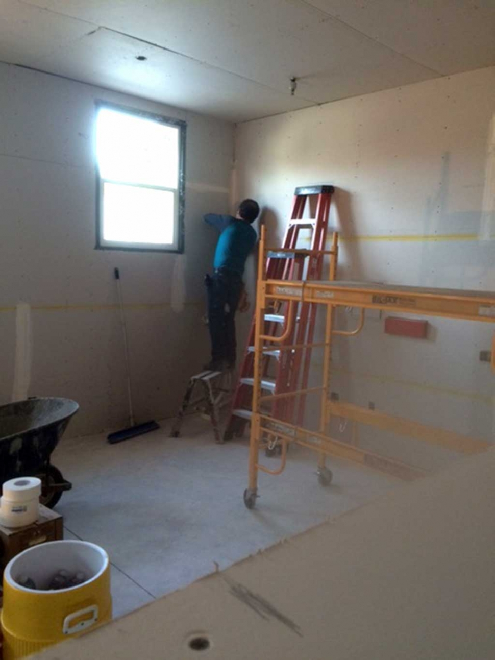 Salvador Alvardo from Local #150 applies the drywall tape, mud and texture to the so to be Teen Study Center at the Boys & Girls Club.