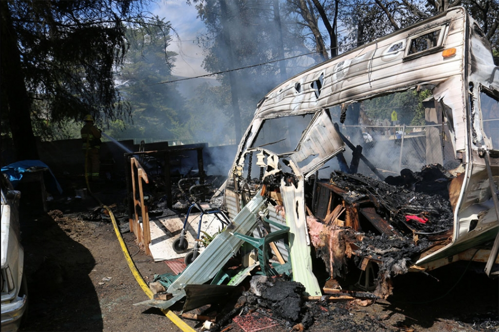 Fillmore Fire Department assisted Ventura County Fire last Wednesday, with a fire in the 4400 block of Santa Paula Ojai Road, near Mupu School. The fire apparently started near a small trailer, pictured above. The trailer was destroyed, two other vehicles were engulfed, and a large Pine tree was consumed. The fire was reported at 1:40 p.m., and knocked down by 2 p.m. One man received moderate to severe burns and was transported to a hospital. Photo courtesy Sebastian Ramirez.