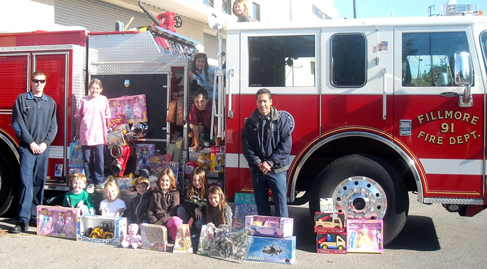 Students from San Cayetano collected items for the annual Kids Give Sale. Pictured are Chad Hope, Tori Villegas, Sara Uriel, Kasey and Dylan Crawford, Cali and Ty Wyand,  Rachel, Victoria and Julia Pace, along with Captain Al Huerta and an unknown fireman, left.