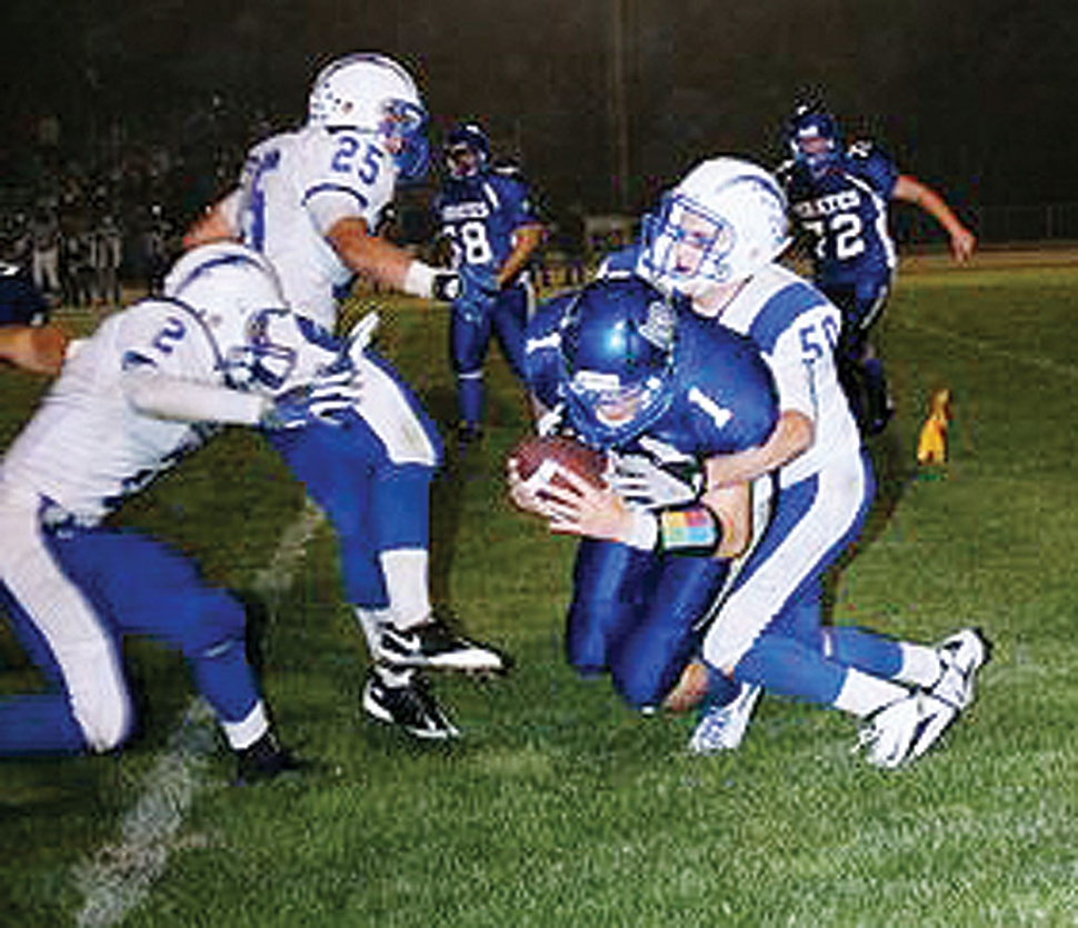 Varsity player Johnny Wilber #50, tackles Morro Bay's quarterback on a run. Also pictured Ty Casey #2 and Austin Davis #25.