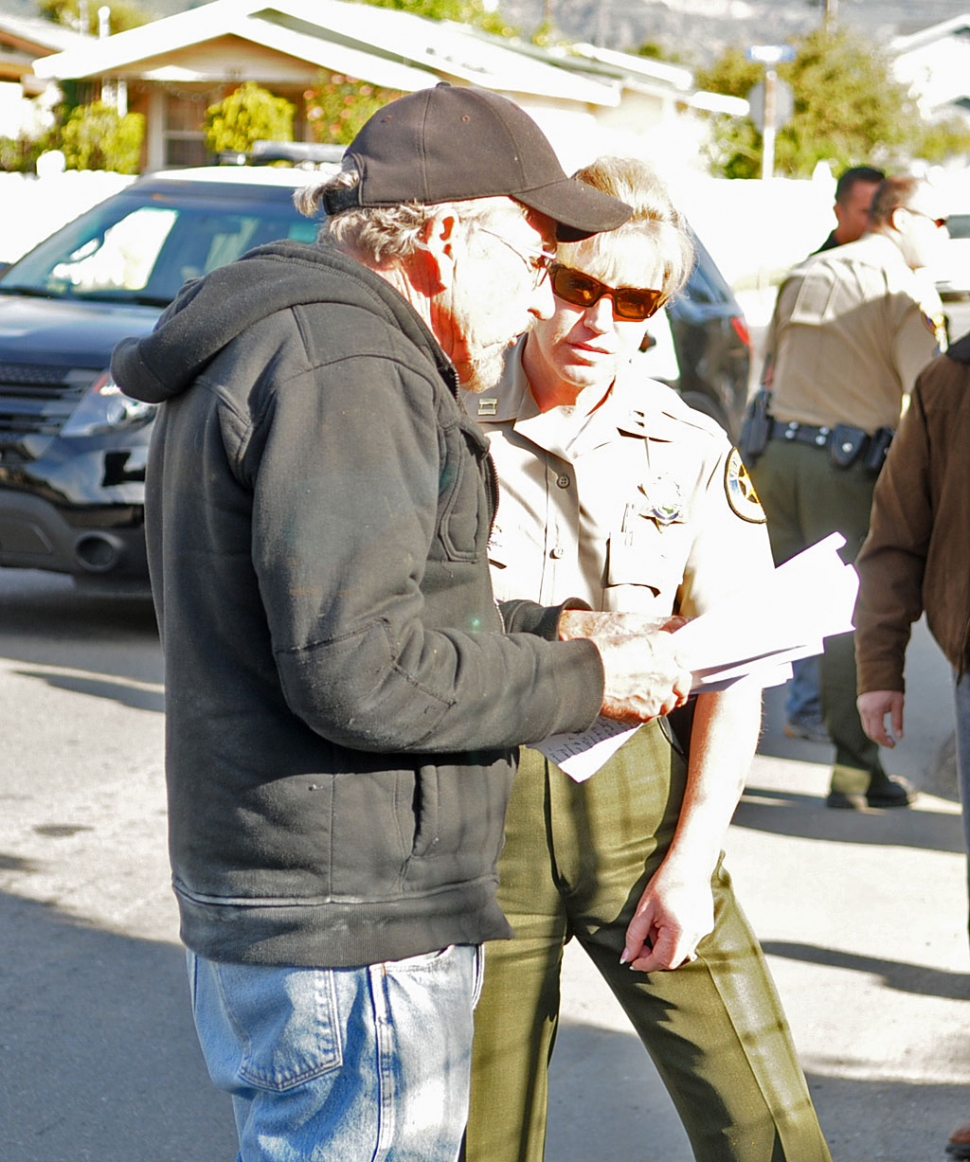 Sheriff's Capt. Monica McGrath speaks with property owner Herbert Haase, as he holds the warrant served on him. Haase has refused to spray his citrus grove for the Asian Citrus Psyllid, an invasive, aphid-like pest.