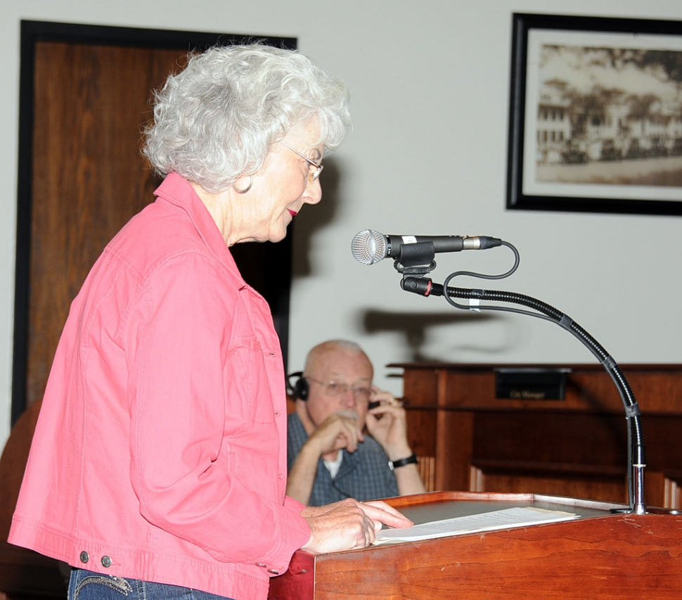 Jean Westling, speaking at the October 9, 2012 council meeting, with husband Clay Westling in background with headphones.