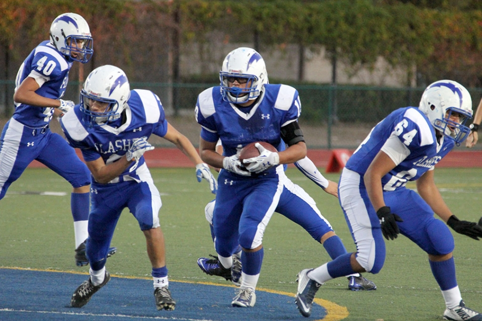 J.V. #10 Daniel Tafoya runs for a first down while gaining blocks from #5 Jose Perez and #64 Angel Medina