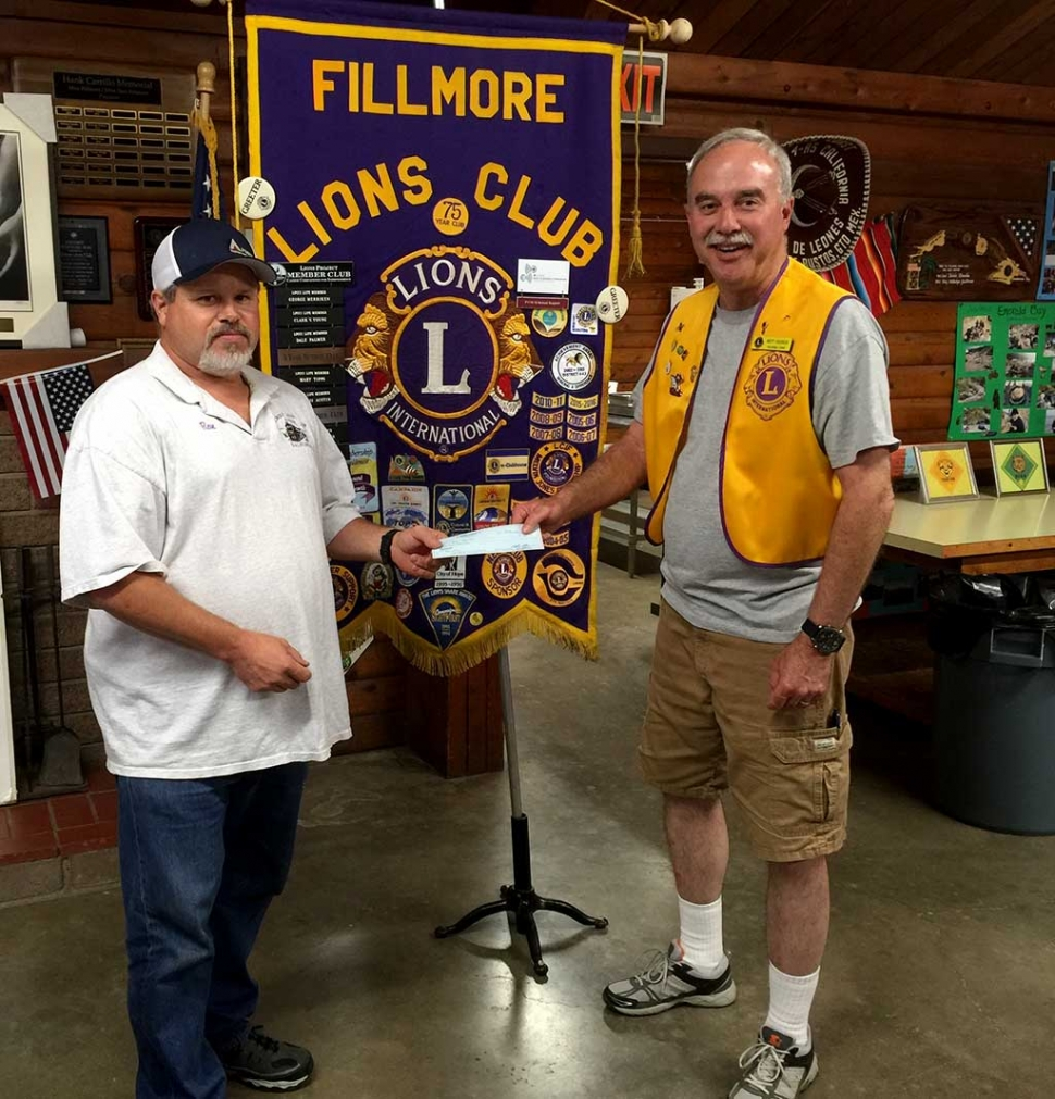 Brett Chandler, Scout Master for Fillmore Troop 406 and treasurer for the Fillmore Lions Club, accepts a $500 check from Lion Ron Smith at a recent meeting. The lions support the troop which shares the scout clubhouse with he Lions club.