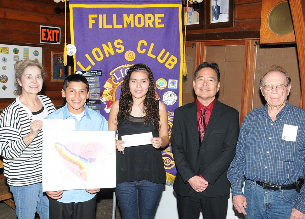 "Aries Vega (holding poster), Fillmore Middle School student, has taken the first step to becoming a state wide recognized artist by winning the local competition sponsored by the Fillmore Lions Club. This year's theme was ""Imagine Peace"". Aries' work was selected from the work of students in Doris Nichols' (far left) art classes. Aries' poster has been forwarded to the local Lions District for further competition in California. When Aries was asked how his poster represented the theme he responded, ""Peace is what you do and see in the world and what to expect from it"". The runner-ups were Leonardo Rodriquez and Markayla Aguilar (holding certificate). Aries received $50 as the winner and Leonardo and Markayla $25. Judges Todd DeMheen and Ken Mittan (far right) were impressed by the many fine posters submitted. They also want to encourage all students to participate again next year. Also pictured Fillmore Middle School Principal Gary Mayeda."