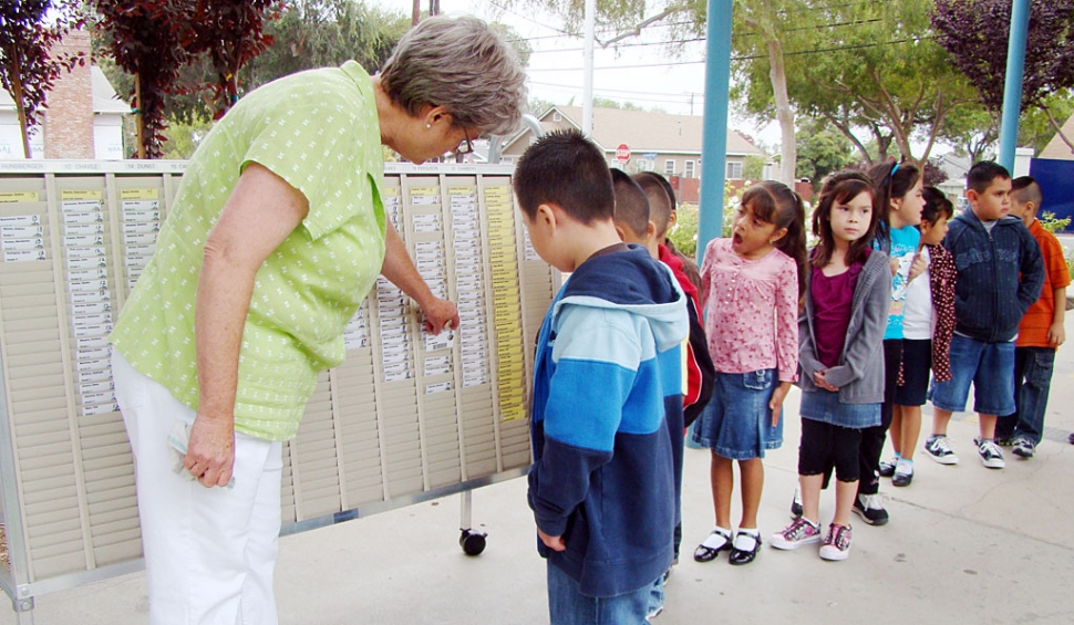Ruth Ricards, Director of Child Nutrition for Fillmore Unified School District, is showing San Cayetano students how to find their name for their lunch scan card. There is a new technology scanning system in the elementary schools this year. The students find their teacher, find their own name on a card, then scan it and proceed to lunch. It appears that the students enjoy looking for their own card.