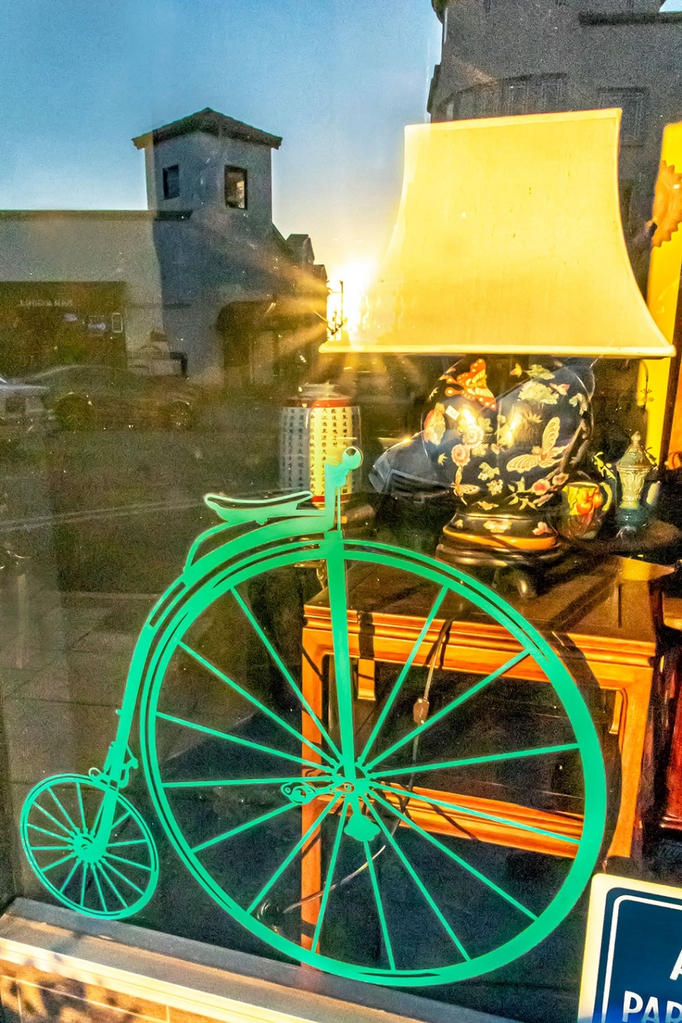 "Photo of the Week: ""Sun reflection on green unicycle in Central Avenue shop window"" by Bob Crum. Photo data: Canon 7D MKII camera, manual mode with Tamron 16-300mm lens @16mm. Exposure; ISO 16000, aperture f/22, 1/500th second shutter speed."