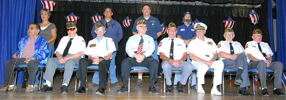 Fillmore's war heroes honored at Middle School's Pride in America Day. From left, Fred Ortiz, Wendell Tilley, Richard Schuck, J. C. Woods, Jim Rogers, Don Gunderson, Bud Untiedt, and John Pressey. Standing (l-r) Ortiz' daughter Julia, and veterans Gama Aguilar, Jess Garnica, and Vincent Cobb. This year's program was attended by a disciplined and respectful student audience, and addressed by honored guest speaker Staff Sergeant Felix Gabriel Chavez, U.S. Army.