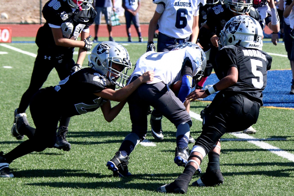 Fillmore Raiders Bantam Black's #22 and #25 making a tackle in their game this past Saturday against Saugus.