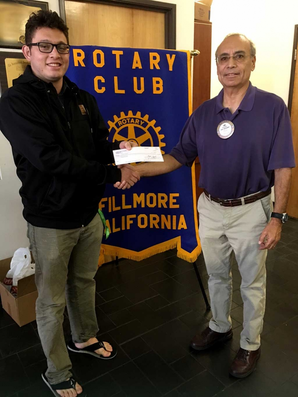 Jacob Brooks, Vice President of FHS Band Boosters Club, accepted a check from Rotarian Joe Aguirre, chairman of 5/10K Run. This donation came from Santa Clarita Runners Club who enjoys giving back to Fillmore youth.