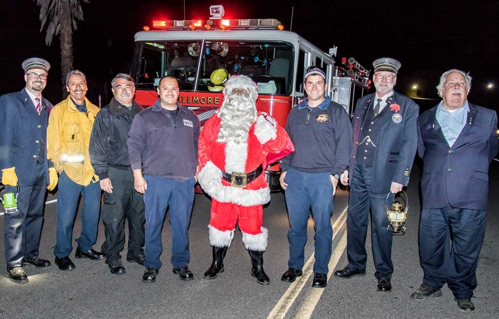 (l-r) Train Conductor Ryan Stern, Captain Al Huerta, Chief Gurrola, Firefighter Salazar, Santa, Firefighter Lechnar, Steve Phares, and Dave Wilkinson gather to take a photo with Santa. Traveling all the way from the North Pole, Santa arrives in Fillmore on the Fillmore & Western Railway Santa Train. And just in time for ole St. Nick to join the fantabulous Lions Club Christmas Parade Saturday, 12/3/16 at 1 p.m. Photo by Bob Crum.