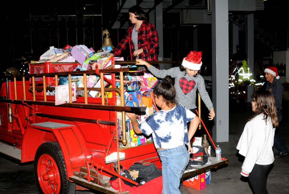Above are some of the toys that were collected from last year's Holiday Toy Drive with Santa's helpers loading up the truck.