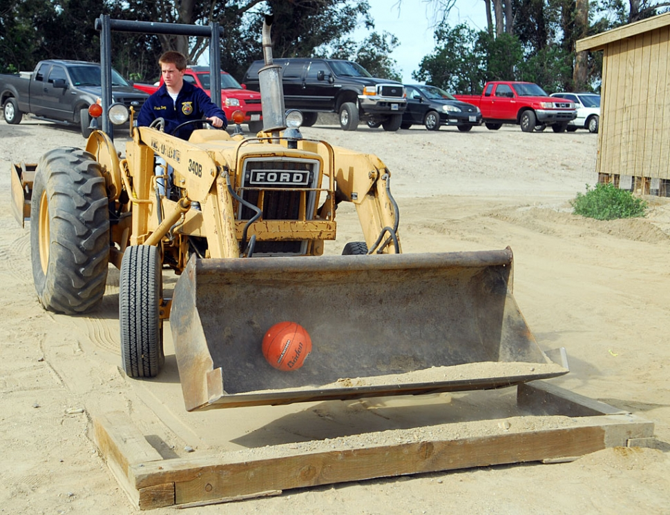 Among the various events at Saturday's School Farm was a demonstration of skill with a front loader. Here Travis Doop from Carpinteria must pick up a basketball from a pit and re-place it without dropping or