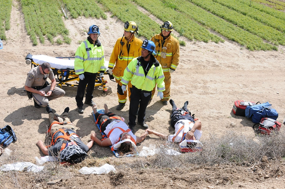 Three victims wait to be transported at the base of a 10-foot ravine. The vehicle they were riding in went down the ravine and came to rest at the edge of a crop field.