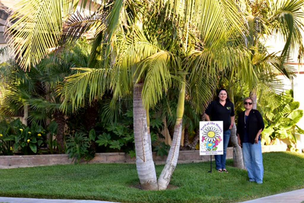The June Yard of the Month has a tropical feel. Pictured (l-r) Lorena Jimenez and Ari Larson. Photo courtesy Ari Larson.